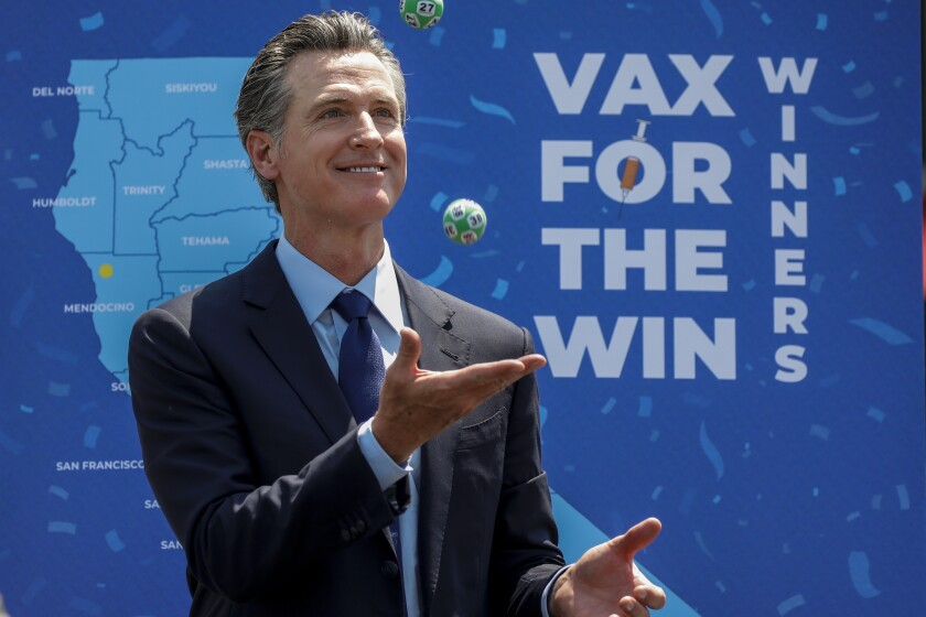 Gov. Gavin Newsom juggles numbered balls used in a lottery-style give away, following the conclusion of a press conference