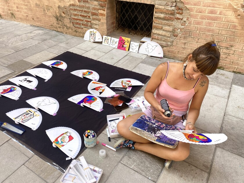 A woman sits on the ground while crafting souvenir fans