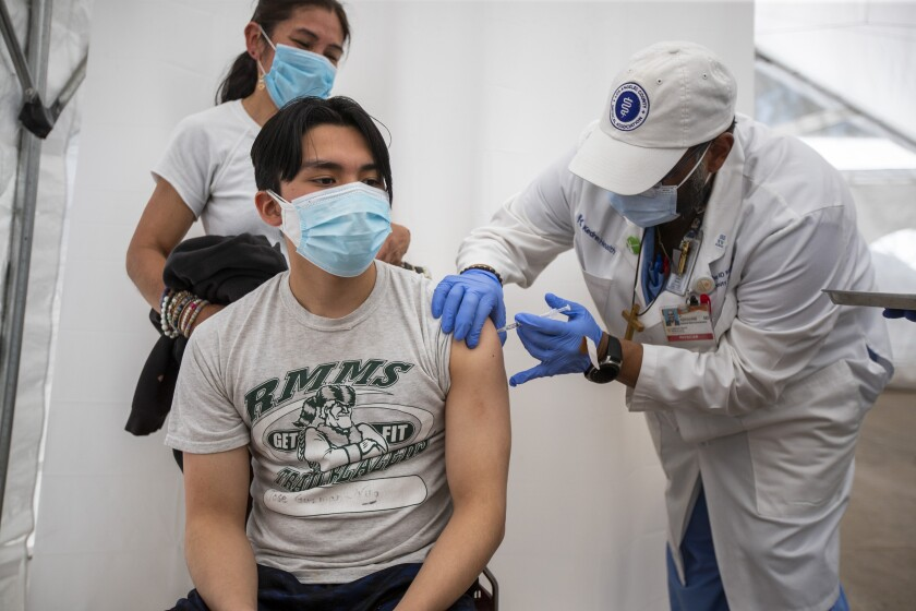 LOS ANGELES, CA - April 15: Dr. Jerry Abraham, director of Kedren Vaccines, right, gives a COVID-19 vaccination to Jose Guzman-Wug, 16, while his mom, Adriana Wug, watches at Kedren Health on Thursday, April 15, 2021 in Los Angeles, CA. Award-winning television producer, Marti Noxon, who's a big fan of Kedren Vaccines, sent an In-N-Out truck to feed 200+ volunteers who help make this vaccine program such a huge success and she did so on the day that vaccines are being made available to all people 16+ in Los Angeles. (Allen J. Schaben / Los Angeles Times)