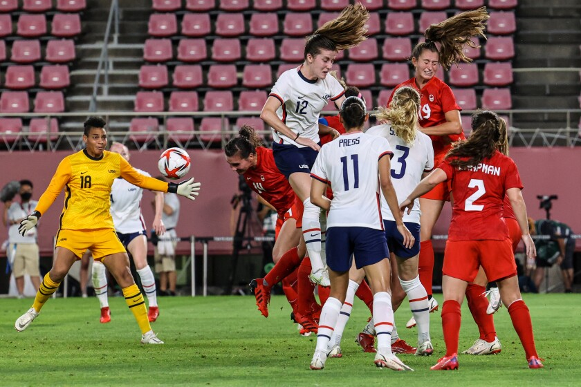 U.S. players try to hold back a Canada scoring attempt late in Monday's Olympic semifinal match.