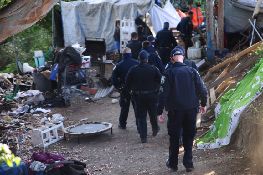 Police move through the Highway 1/9 encampment Monday morning to begin the eviction process.