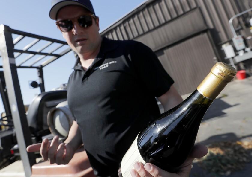 Dominic Foppoli holds a bottle of wine.
