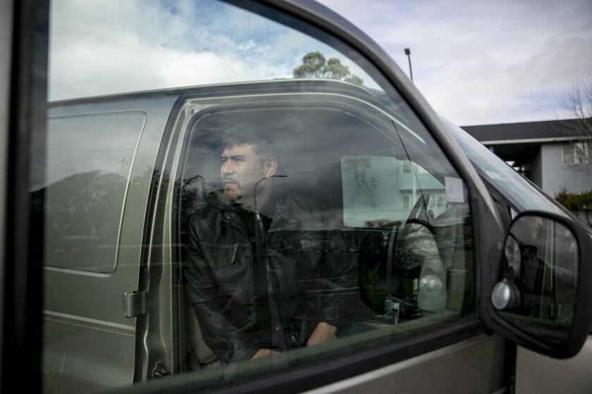 Guillermo Hernandez sits in his van in Richmond