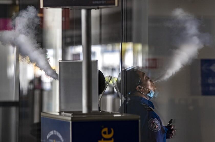 TSA agent Pierre Tuble enjoys a quick vape on a break at LAX on Thursday, Dec. 31, 2020 in Los Angeles, CA.