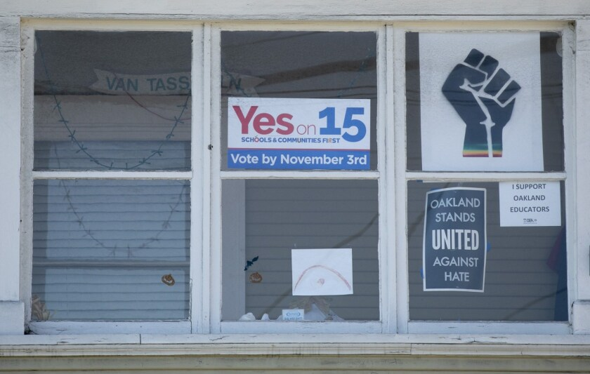 Signs supporting Prop 15 and Oakland Schools hang in the window of a home in Oakland on Oct. 31, 2020.