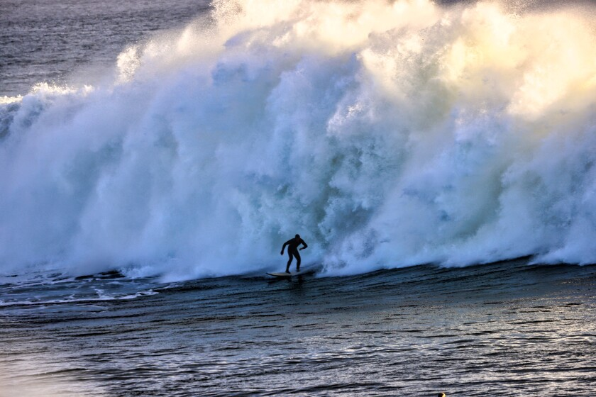 A surfer takes on massive swells on Dec. 8, 2020.