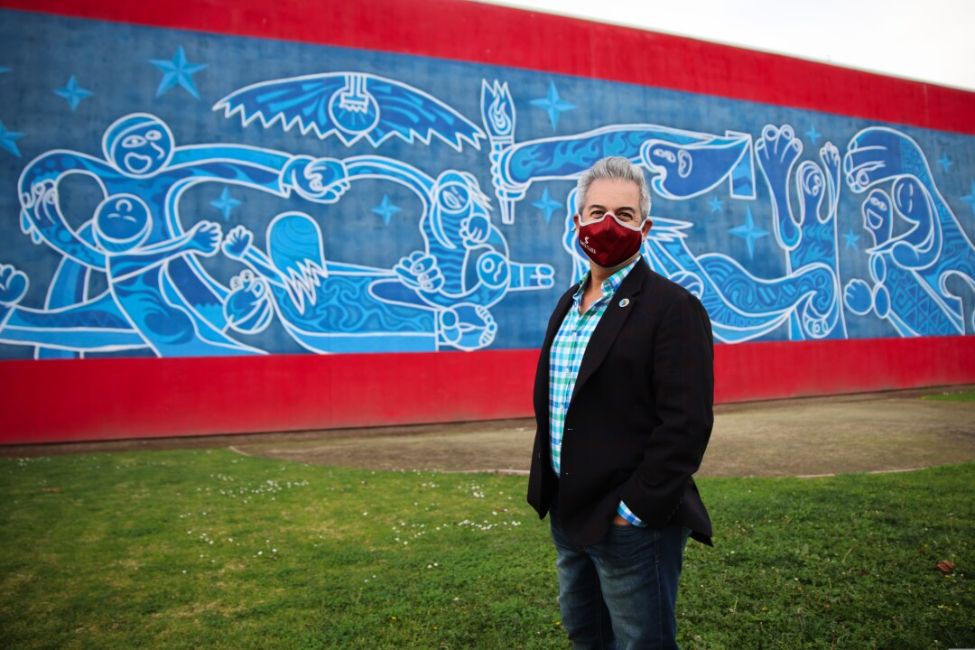 Watsonville Mayor Jimmy Dutra stands in front of a mural in his city.