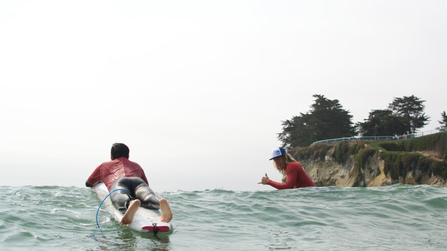 Adventure Out's Chase LaRue gives his student a shaka after riding a wave at Cowell Beach.