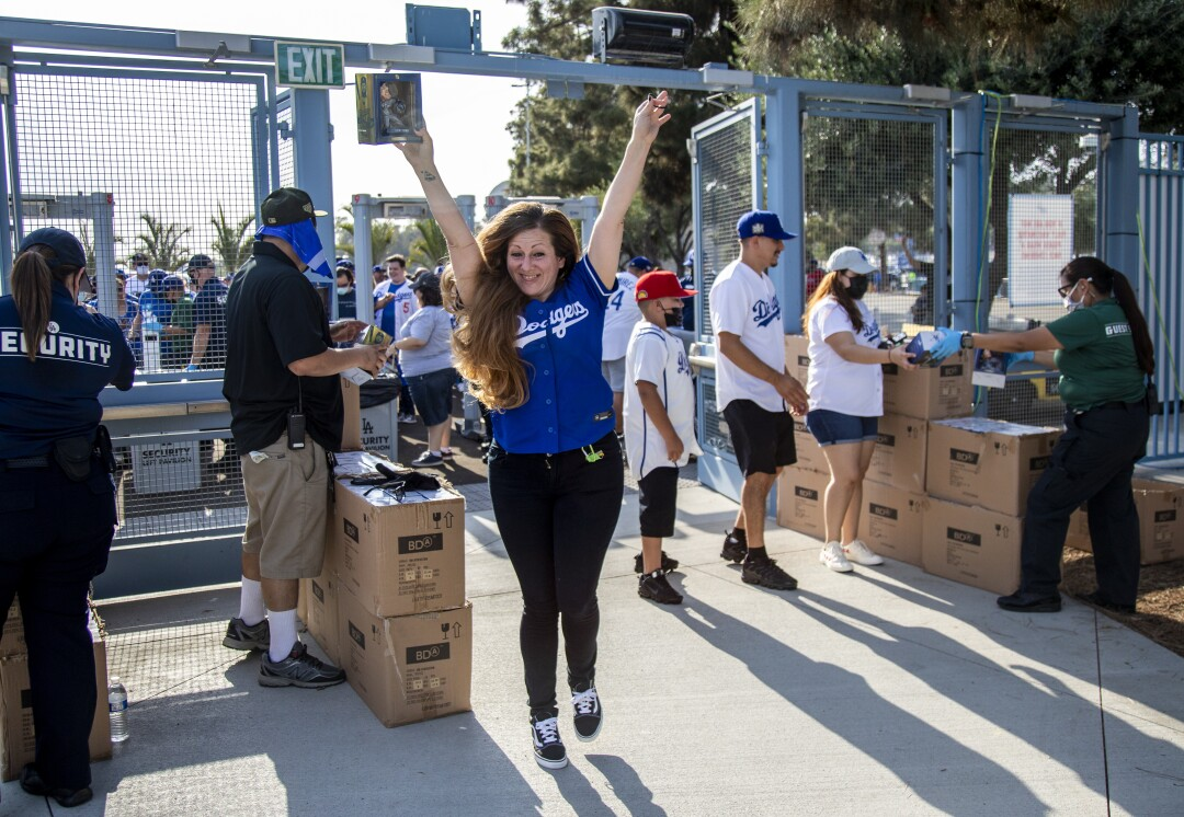 A woman in a Dodgers shirt raises her arms
