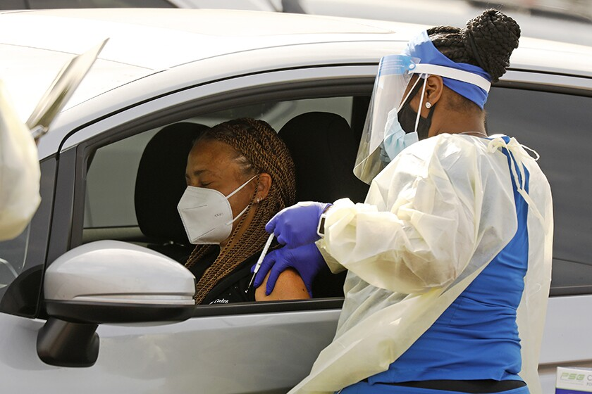 A motorist receives the COVID-19 vaccine at The Forum in Inglewood .