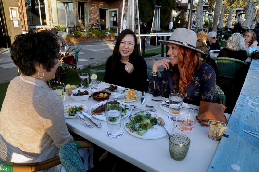 REDONDO BEACH, CA - APRIL 27: Sheryl Rasmussen, of Rancho Palos Verdes, left, Eileen Yun, of Rancho Palos Verdes, and Kristy Langus, of Palos Verdes Estates, dine along S. Catalina Ave on Tuesday, April 27, 2021 in Redondo Beach, CA. They all came out to dinner because they are all fully vaccinated. They said if they were not vaccinated they would not have come out. U.S. health officials say fully vaccinated Americans don't need to wear masks outdoors anymore unless they are in a big crowd of strangers (Associated Press). (Gary Coronado / Los Angeles Times)