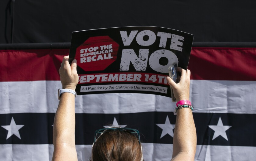 A Gavin Newsom supporter holds up a sign against the recall at a campaign event