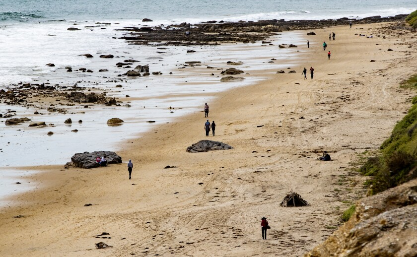 People walk on Newport Beach beach