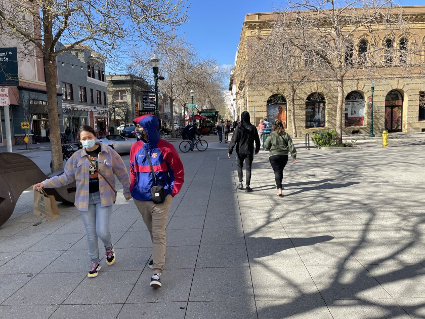 People take to the sidewalks along Pacific Avenue in downtown Santa Cruz on Saturday, March 13, 2021.