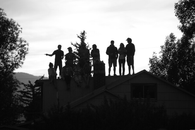 a black and white photo of people standing on a roof