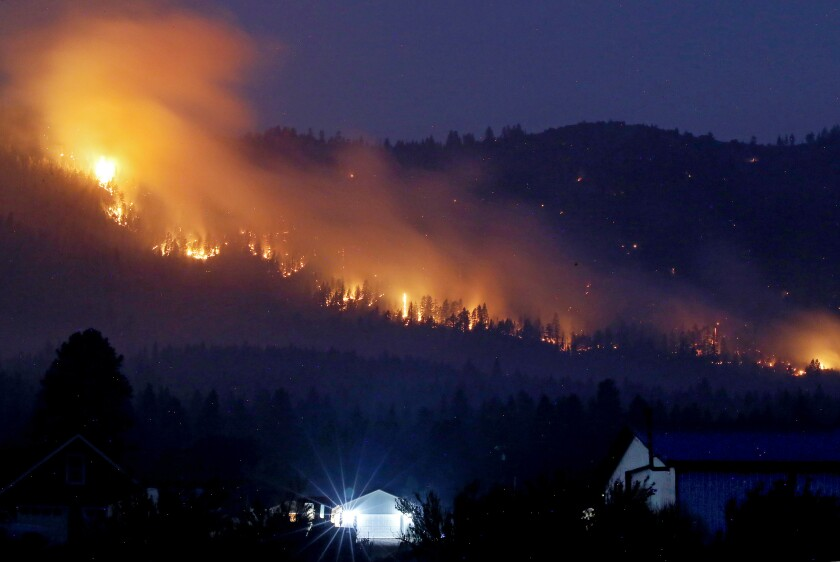 Flames burn through trees on a mountainside at night