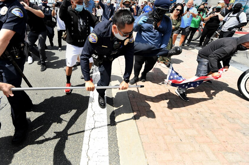 A young man steals an American flag from a White Lives Matter supporter as a Huntongton Beach police officer tries to stop it