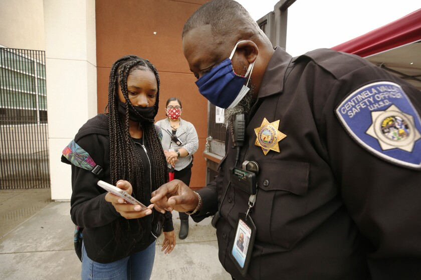 A school safety officer in a uniform with a badge views the screen of a student's phone. Both wear masks.