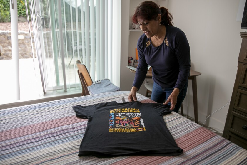 Martha Garrido lays out a California Domestic Worker's Coalition shirt on the bed at her San Francisco home.