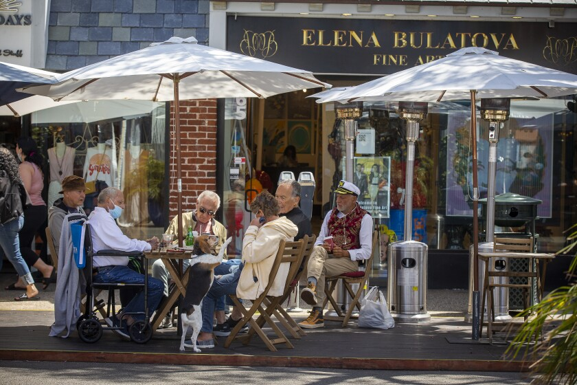 Harry Brown, left, and his wife, Kathy Schaefer, of Laguna Beach, join friends dining and watching pedestrians walk by