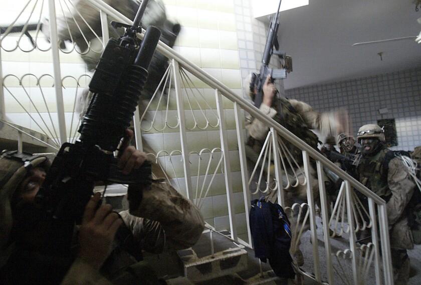 Marines point guns upward in a house