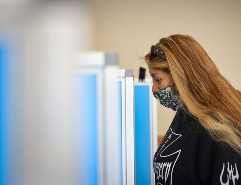 A woman wears a mask as she casts her vote on Election Day in Santa Cruz County on Nov. 3, 2020.