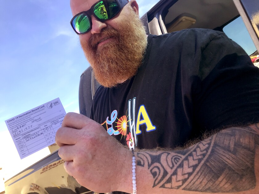 Shane Curran shows off his vaccine card after getting his shot