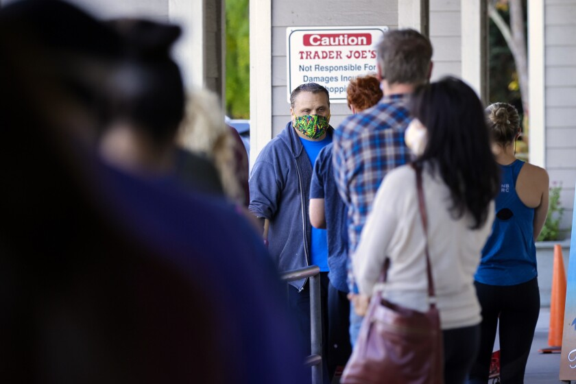 Masked shoppers wait in line at Trader Joe's in Capitola on Monday.