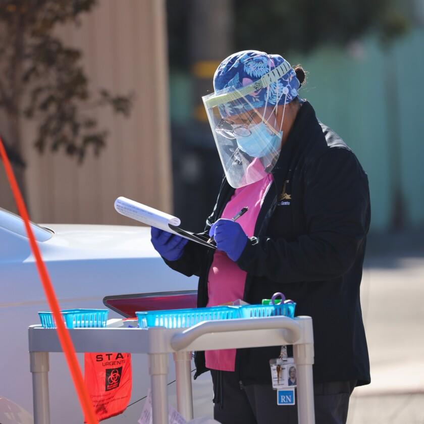 A nurse checks a clipboard at a COVID-19 testing facility in Santa Cruz County.