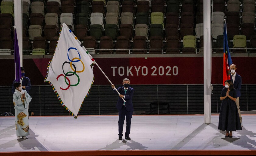 Thomas Bach, president of the International Olympic Committee, waves the Olympic flag.