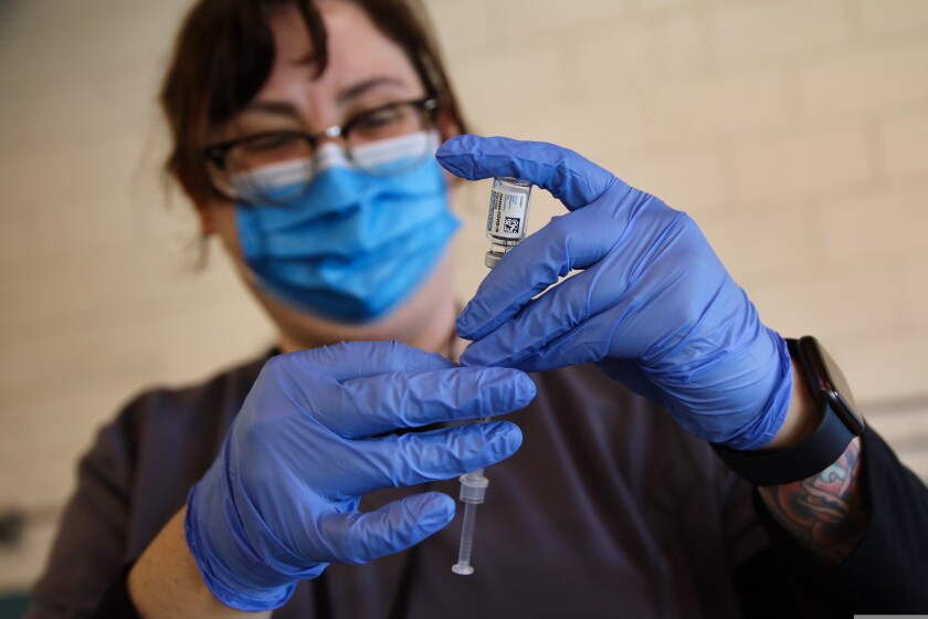A health care worker prepares a dose of the Janssen COVID-19 vaccine