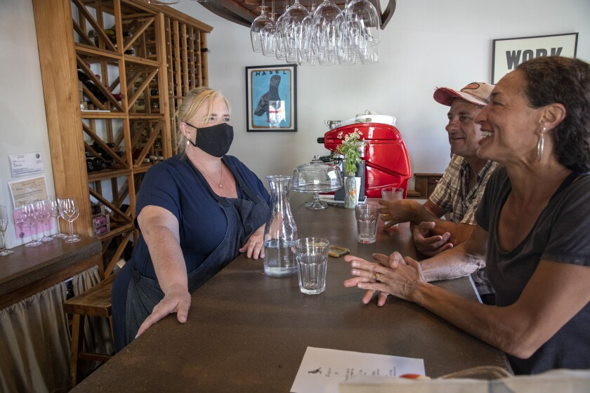 Hazel owner Michele Wimborough, left, chats with guests Rahna Schiff, right, and Keith Holamon, cente