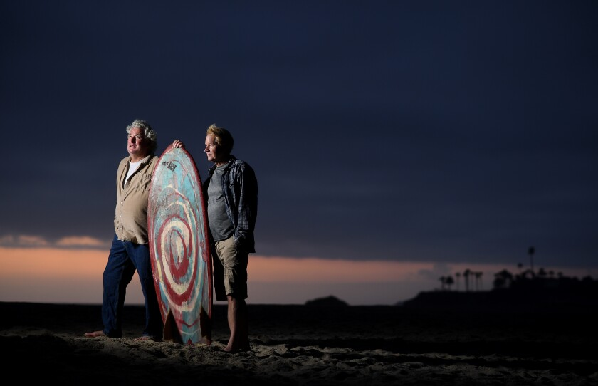 Surfers Kevin Naughton, left, and Craig Peterson stand on the sand in Laguna Beach.