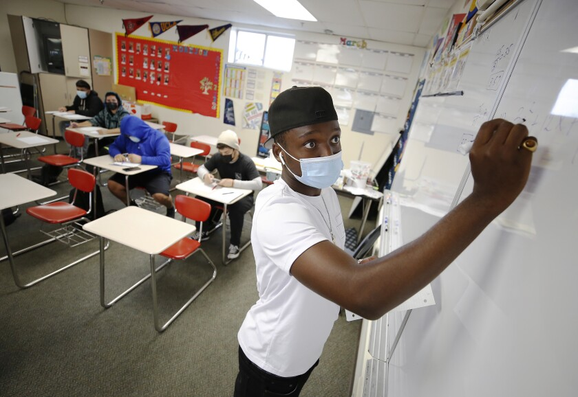 A masked student writes on a whiteboard
