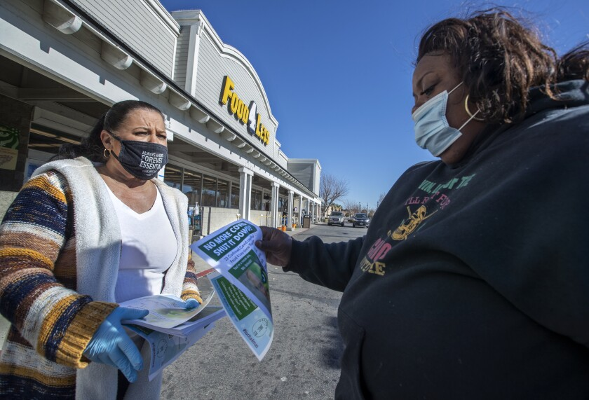 A grocery store cashier hands a flyer to a customer outside Food 4 Less in Palmdale.