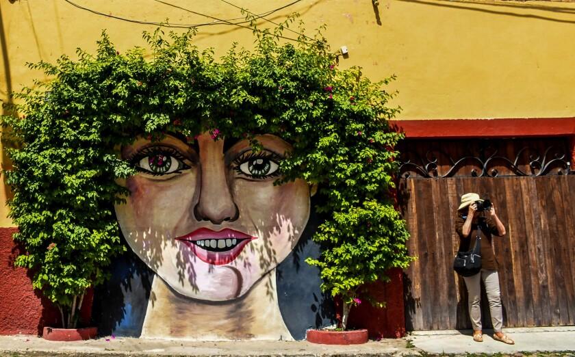 A tourist stands beneath a mural in San Miguel de Allende, Mexico.