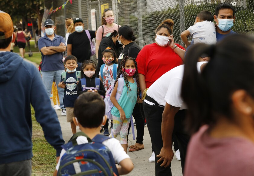 Parents and children form lines to check for student names on a COVID health clearance list at an elementary school