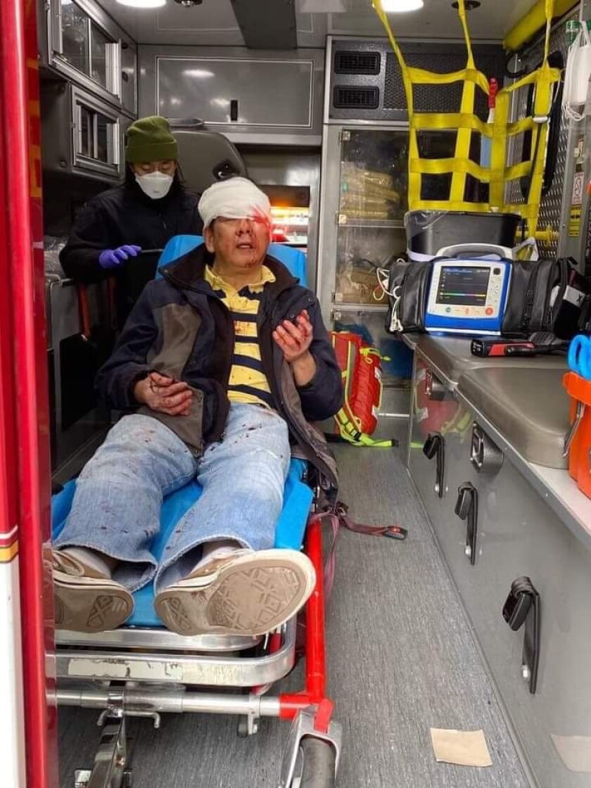 Danilo Yuchang, 59, sits in an ambulance with a white bandage around his head.