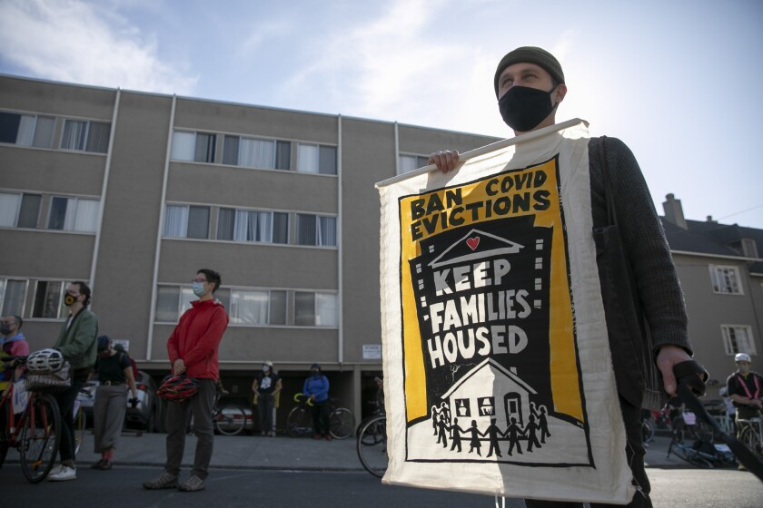 Oakland resident Andrew Rosenburg holds up a banner while protesting rent evictions during the pandemic on Dec. 5, 2020 in Oakland. Photo by Anne Wernikoff, CalMatters