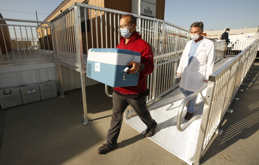 Emergency Medical Technician Lenny Fernandez carries a cooler specialized for the delivery of the Pfizer COVID-19 vaccine