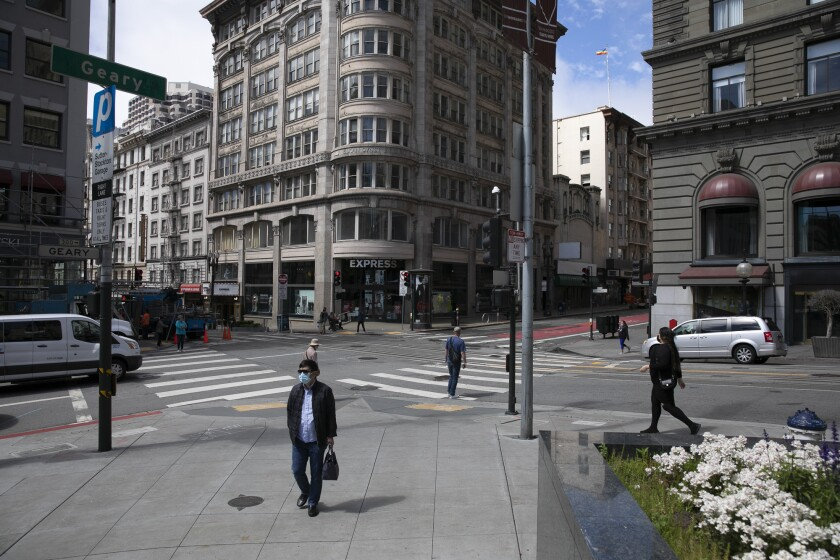 Pedestrians walk through union square in San Francisco on June 14, 2021. The intersection of Geary and Powell Streets would have been busy with traffic, street cars and throngs of foot traffic before the pandemic. Photo by Anne Wernikoff, CalMatters