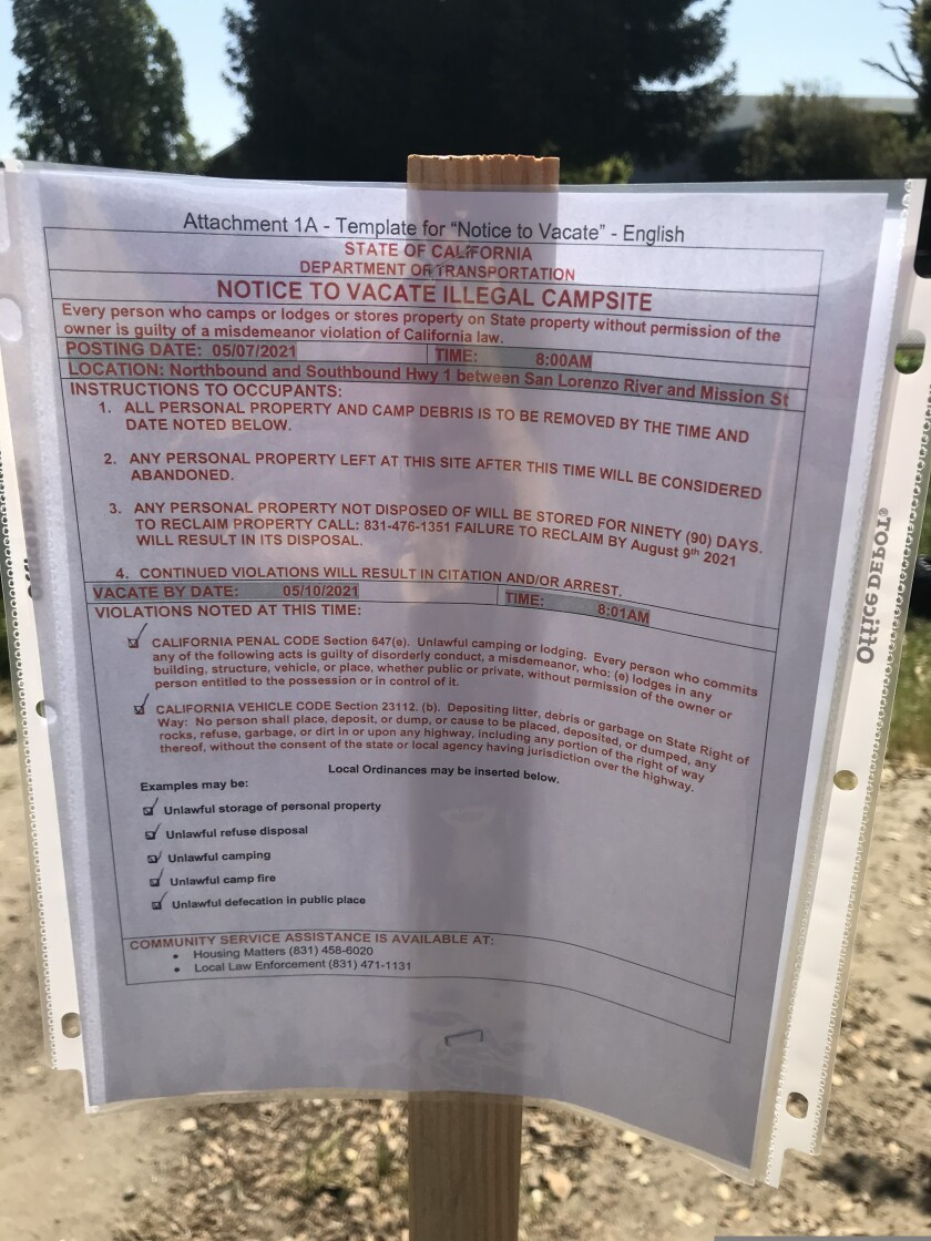 """One of the notices """"to vacate illegal campsite"""" that went up at Highways 1 and 9 on Friday."""