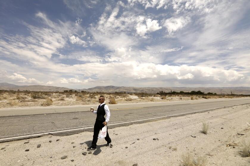 Roger Embrey walks to a job interview along a desert road