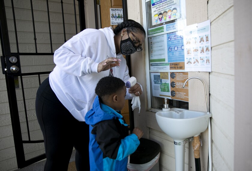 Family daycare provider Lucre-ce Lester takes a student's temperature