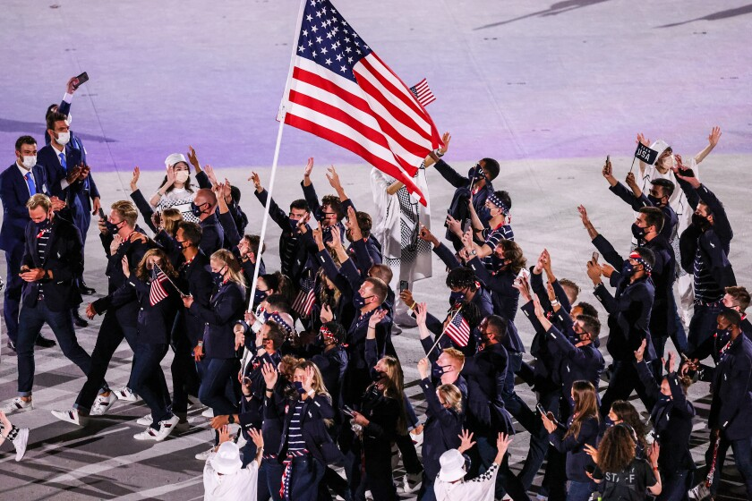 U.S. athletes wave surrounding the flag during the Tokyo Olympics opening ceremony.