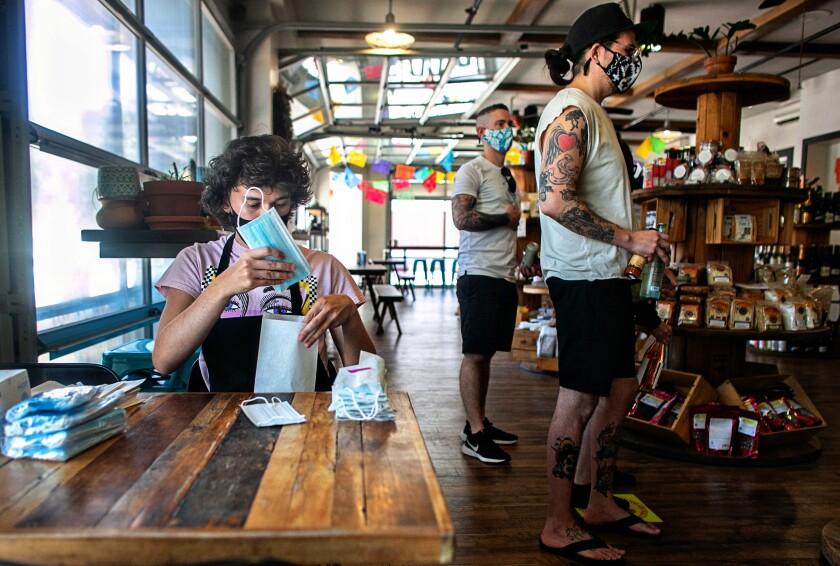 A worker prepares individual packets of masks at Alta Baja Market in Santa Ana