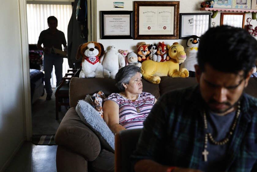 SANTA ANA, CALIFORNIA: Jonatan Gutierrez, 32, right, and his parents Rocio Urzua, 54, center, and Pablo Gutierrez, 65, at left, are photographed at home in Santa Ana, California on Friday, July 2, 2021. Medi-Cal expansion will offer relier to income eligible adults 50 and older regardless of immigration status. (Christina House / Los Angeles Times)
