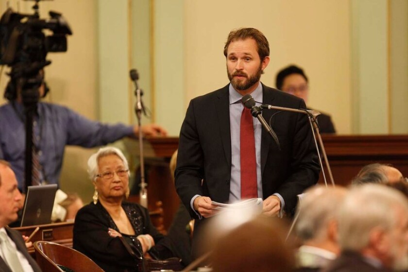 James Gallagher speaks into a microphone on the Assembly floor.