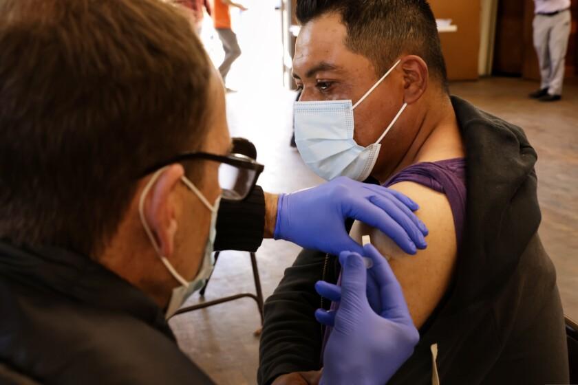 A Santa Cruz County farmworker, Ivan Ramirez, receives a Pfizer-BioNTech vaccine shot by Physician Greg Whitley