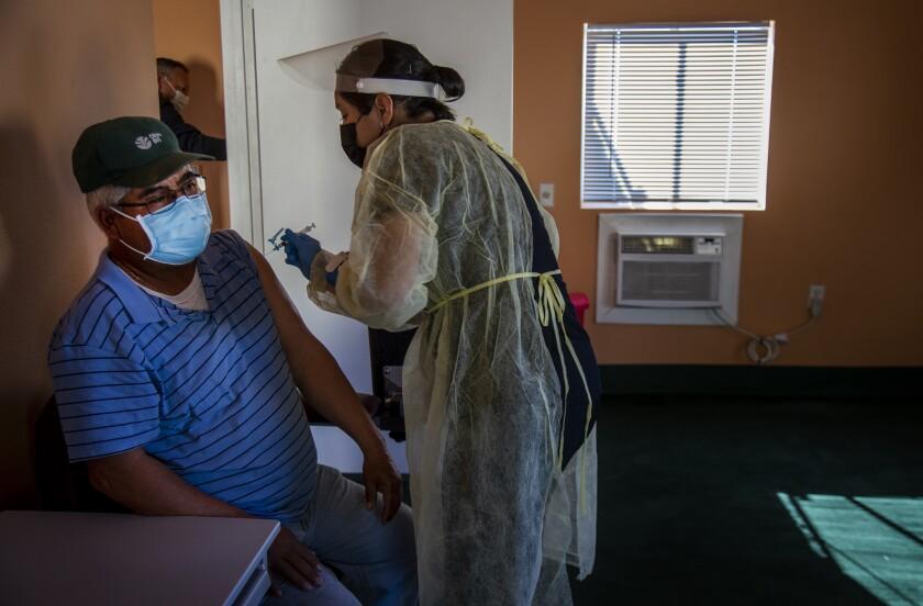A farmworker receives a dose of the COVID-19 vaccine.